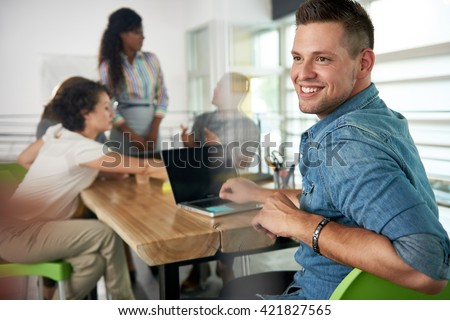 Image of a succesful casual business man using laptop during meeting