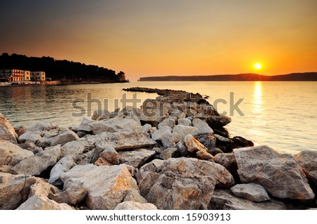 Image of a sunset in the town of Pylos, southern Greece, with rocks in the foreground and the island of Sfaktiria in the background - stock photo