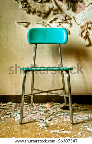 Image of a teal blue chair in an abandoned building with cracked and peeling paint illuminated by natural daylight with hard shadow. - stock photo
