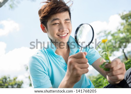 Image of a teenager looking at the flower through the magnifier outside - stock photo