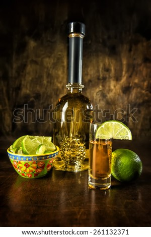 Image of a tequila bottle, shot with lime and lime wedge - stock photo