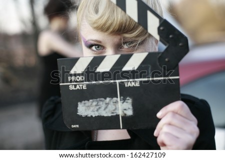 image of a the girl in the film production with clapperboard, young woman holding clapperboard - stock photo