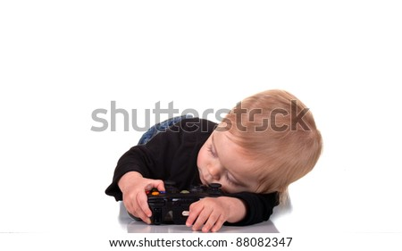 Image of a tired baby holding a gaming controller. - stock photo