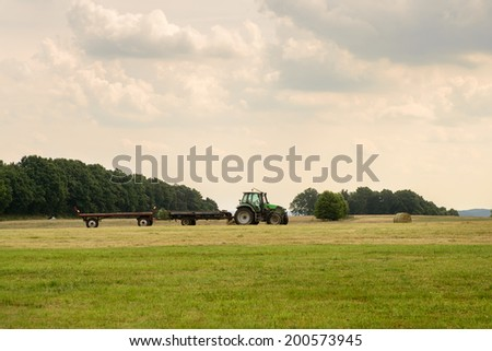Image of a tractor and trailers in a field during farming season