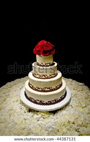 Image of a traditional four tiered wedding cake with red roses on top sitting on a bed of white roses