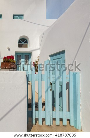 Image of a traditional white house with blue doors and gate. Santorini, Greece.  - stock photo