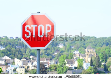 Image of a traffic stop sign with the historical german town of Remagen in the distance