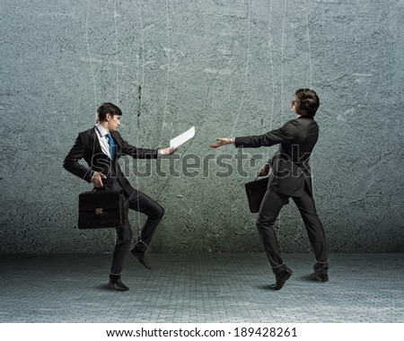 image of a two businessman puppet doll pass each other business papers - stock photo