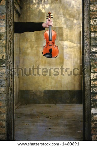 Image of a violin held at arms length in an old doorway.Ideal for wording underneath violin - stock photo