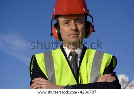 Image of a white collar worker wearing safety equipment. - stock photo