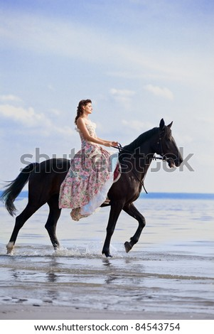 Image of a woman on a horse by the sea - stock photo