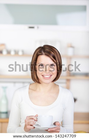 Image of a woman standing with a cup of coffee in the kitchen.