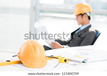 Image of a working contractor with a hardhat and measuring tools in the foreground - stock photo