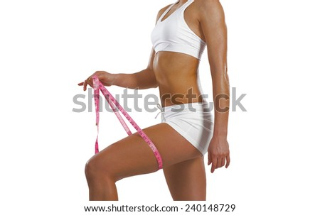 image of a young athletic woman measuring thigh - stock photo