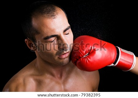 Image of a young boxer man getting punched in the face over black background - stock photo