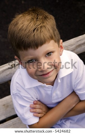 Image of a young boy looking up at viewer - stock photo