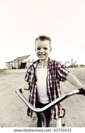 Image of a young boy riding a scooter with a devilish grin. - stock photo