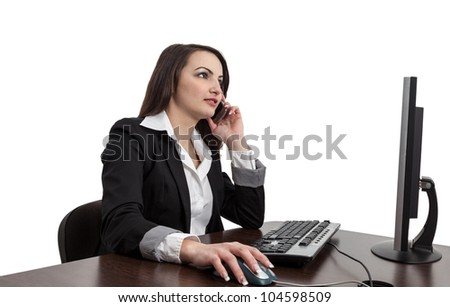 Image of a young brunette woman working on a computer and using a mobile phone , isolated against a white background. - stock photo