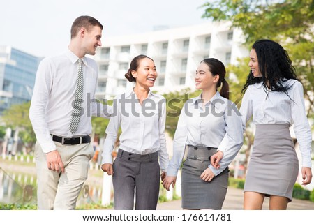 Image of a young business team talking while walking outside  - stock photo