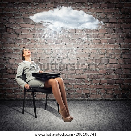 image of a young business woman looking at the cloud with lightning