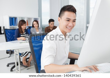Image of a young businessman at work on the foreground