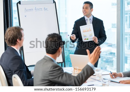 Image of a young businessman explaining the business activity plan and asking his colleague to suggest his decision on the foreground - stock photo