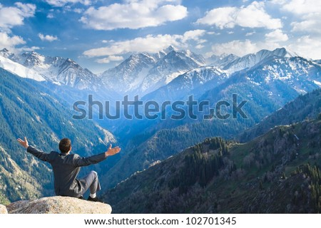 Image of a young businessman who sits on the top of the mountain on the background of the beautiful mountains, relaxing and pleased with the achieved successes.