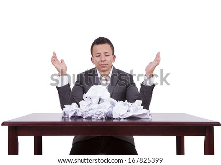 Image of a young businessman with crumpled papers on his desk
