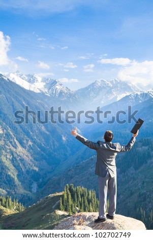 Image of a young businessman with laptop standing at the top of the mountain and looking into the distance to the beautiful mountains, is pleased with the achieved successes. - stock photo