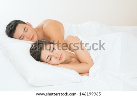 Image of a young couple sleeping in the bedroom