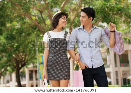 Image of a young couple walking in the park after shopping - stock photo