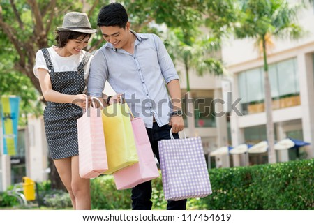 Image of a young couple with shopping bags outside - stock photo