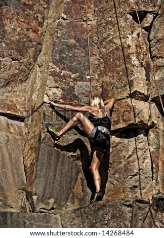 Image of a young fit female Rock Climber - stock photo