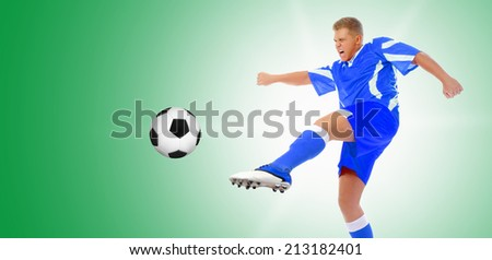 Image of a young football player with the ball in the blue uniform - stock photo