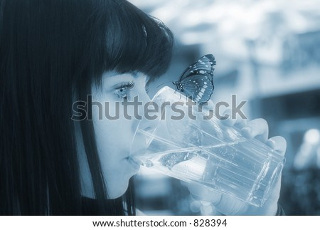 Image of a young girl drinking water with a butterfly perched on the glass - stock photo