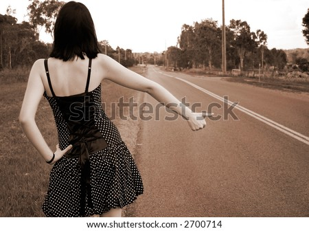 Image of a young girl hitch hiking. - stock photo