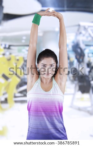 Image of a young indian woman workout in the fitness center and doing warm up by stretching her hands - stock photo