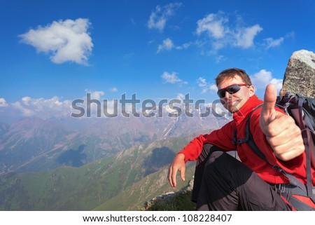 Image of a young man - a tourist, which sits on top and looks into the camera. In the background the snowy mountain tops of the clouds. Tibet in the Himalayas.
