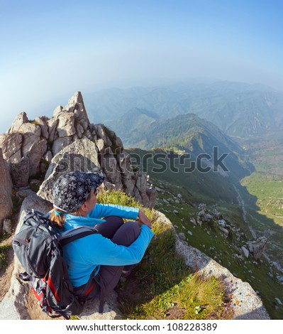 Image of a young woman - a tourist, which sits on top and looks into the maountains. In the background the snowy mountain tops of the clouds. Tibet in the Himalayas. - stock photo