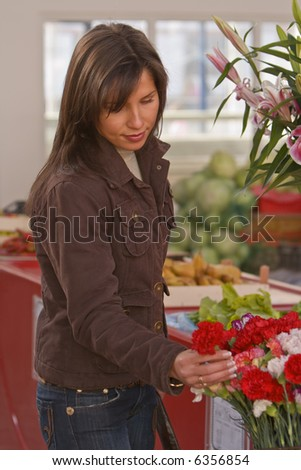 Image of a young woman buying flowers in a market.