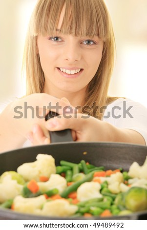 Image of a young woman cooking healthy food in the kitchen - stock photo