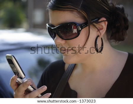 Image of a young woman looking at her cell phone - stock photo