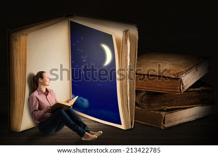 image of a young woman reading a book sitting near a big book