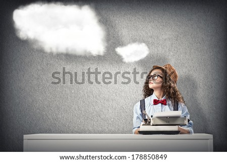 image of a young woman writer at the table with typewriter - stock photo