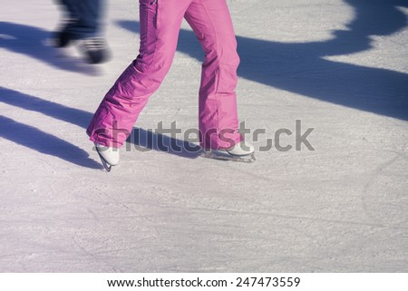 Image of adults feet who are ice skating, wearing pink pants - stock photo