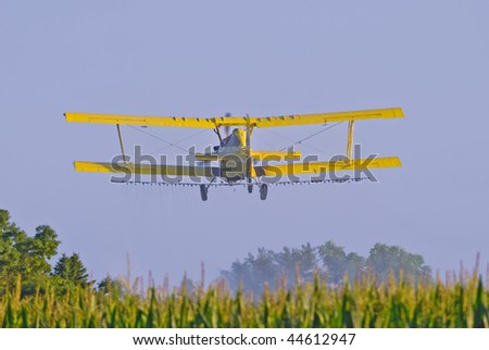 Image of aerial crop duster spraying corn field in rural Iowa. - stock photo