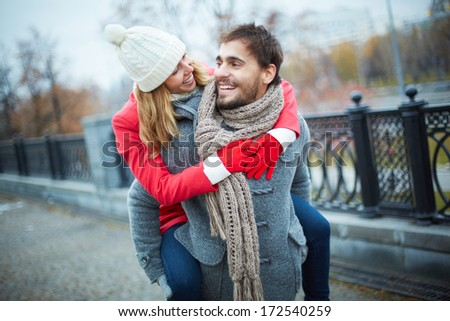 Image of affectionate girl on her boyfriend back in park - stock photo
