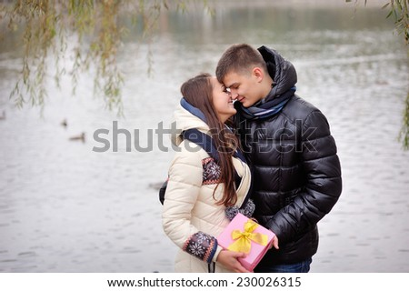 Image of affectionate guy kissing his girlfriend while giving her present outside. - stock photo