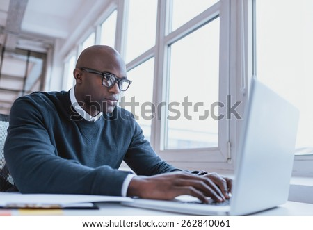 Image of african american businessman working on his laptop. Handsome young man at his desk. - stock photo