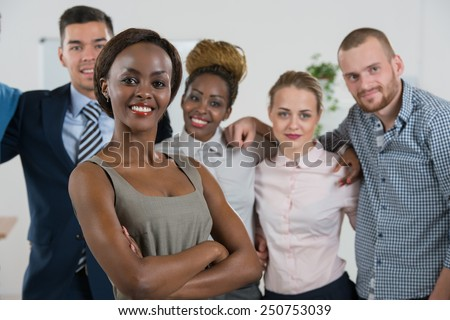 Image of African-American female business leader in front of her business team - stock photo